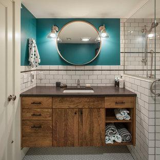 Inspiration pour une salle de bain traditionnelle avec un placard à porte plane, des portes de placard en bois sombre, un carrelage blanc, un carrelage métro, un mur bleu, un sol en carrelage de terre cuite, un lavabo encastré, un sol blanc et un plan de toilette marron.