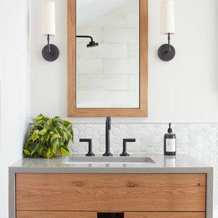 Ejemplo de cuarto de baño contemporáneo con armarios con paneles lisos, puertas de armario de madera oscura, paredes blancas y lavabo bajoencimera
