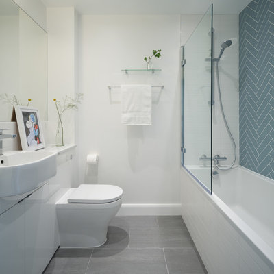 Bathroom - scandinavian 3/4 blue tile gray floor bathroom idea in London with flat-panel cabinets, white cabinets, a one-piece toilet, white walls, a drop-in sink, marble countertops and gray countertops