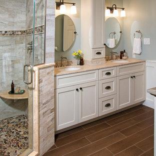 Пример оригинального дизайна: большая главная ванная комната в стиле кантри с плоскими фасадами, бежевыми фасадами, ванной на ножках, угловым душем, раздельным унитазом, бежевой плиткой, керамогранитной плиткой, синими стенами, полом из керамогранита, врезной раковиной, столешницей из известняка, коричневым полом и душем с распашными дверями