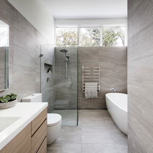 Design ideas for a large contemporary master bathroom in Sydney with a freestanding tub, a curbless shower, a one-piece toilet, gray tile, porcelain tile, white walls, porcelain floors, an undermount sink, engineered quartz benchtops, grey floor, flat-panel cabinets and light wood cabinets.