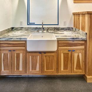 サンフランシスコの中くらいのカントリー風おしゃれな浴室 (落し込みパネル扉のキャビネット、茶色いキャビネット、コーナー型浴槽、シャワー付き浴槽、一体型トイレ、グレーのタイル、磁器タイル、白い壁、磁器タイルの床、アンダーカウンター洗面器、御影石の洗面台、グレーの床、シャワーカーテン、グレーの洗面カウンター) の写真