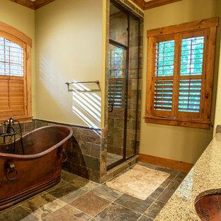 Esempio di una grande stanza da bagno padronale stile americano con lavabo sottopiano, ante con bugna sagomata, ante in legno bruno, top in granito, vasca freestanding, doccia alcova, WC monopezzo, piastrelle multicolore, piastrelle in pietra, pareti gialle e pavimento in ardesia