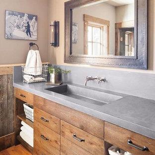 Ispirazione per una stanza da bagno american style di medie dimensioni con consolle stile comò, ante in legno scuro, pareti beige, pavimento in legno massello medio, lavabo integrato e top in cemento