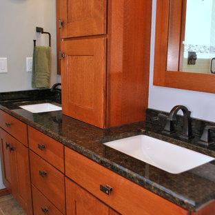 Idée de décoration pour une salle de bain principale craftsman de taille moyenne avec un lavabo encastré, un placard à porte shaker, des portes de placard en bois brun, un plan de toilette en granite, une baignoire encastrée, une douche d'angle, un WC séparé, des carreaux de céramique, un mur bleu, un sol en carrelage de porcelaine et un carrelage multicolore.