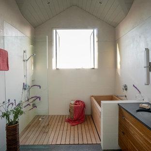 サンフランシスコの広いおしゃれなマスターバスルーム (アンダーカウンター洗面器、フラットパネル扉のキャビネット、中間色木目調キャビネット、ソープストーンの洗面台、和式浴槽、バリアフリー、ベージュのタイル、ベージュの壁、淡色無垢フローリング) の写真