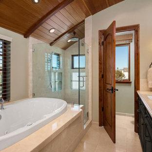 Ejemplo de cuarto de baño principal, de estilo americano, pequeño, con armarios tipo mueble, puertas de armario negras, bañera encastrada, ducha empotrada, sanitario de una pieza, baldosas y/o azulejos beige, baldosas y/o azulejos de piedra, paredes beige, lavabo bajoencimera, encimera de piedra caliza, ducha con puerta con bisagras, encimeras beige, suelo de travertino y suelo beige