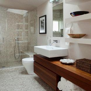 Foto de cuarto de baño con ducha, contemporáneo, grande, con lavabo suspendido, armarios con paneles lisos, puertas de armario de madera en tonos medios, ducha empotrada, baldosas y/o azulejos beige, baldosas y/o azulejos en mosaico, paredes blancas, suelo de baldosas tipo guijarro, encimera de madera, suelo gris, ducha con puerta con bisagras y encimeras marrones