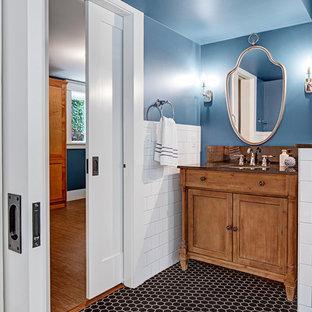 Diseño de cuarto de baño con ducha, de estilo americano, de tamaño medio, con armarios tipo mueble, puertas de armario marrones, ducha esquinera, sanitario de dos piezas, baldosas y/o azulejos blancos, baldosas y/o azulejos de cerámica, paredes azules, suelo de baldosas de cerámica, lavabo encastrado, encimera de cuarzo compacto, suelo negro, ducha con puerta con bisagras y encimeras marrones