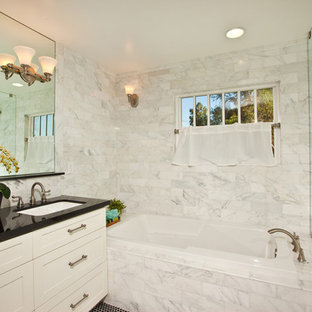 Example of a trendy white tile and marble tile bathroom design in San Diego with white cabinets