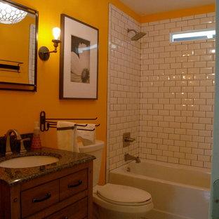 Esempio di una piccola stanza da bagno country con consolle stile comò, ante con finitura invecchiata, vasca ad alcova, vasca/doccia, WC a due pezzi, piastrelle bianche, piastrelle diamantate, pareti arancioni, pavimento in marmo, lavabo sottopiano e top in granito