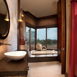 Large world-inspired ensuite bathroom in San Diego with a built-in bath, beige tiles, brown walls, a vessel sink, flat-panel cabinets, dark wood cabinets, an alcove shower, a two-piece toilet, limestone tiles, cement flooring, wooden worktops, beige floors and brown worktops.