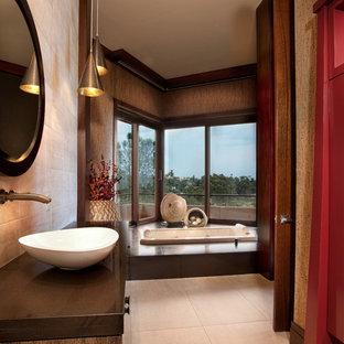Идея дизайна: большая главная ванная комната в восточном стиле с накладной ванной, бежевой плиткой, коричневыми стенами, настольной раковиной, плоскими фасадами, темными деревянными фасадами, душем в нише, раздельным унитазом, плиткой из известняка, полом из цементной плитки, столешницей из дерева, бежевым полом и коричневой столешницей