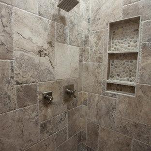 Modelo de cuarto de baño principal, de estilo americano, grande, con lavabo bajoencimera, armarios estilo shaker, puertas de armario de madera en tonos medios, encimera de mármol, bañera encastrada, ducha abierta, sanitario de una pieza, baldosas y/o azulejos beige, baldosas y/o azulejos de piedra, paredes grises y suelo de travertino