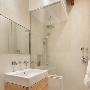 Mid-sized urban master beige tile and porcelain tile ceramic floor bathroom photo in New York with a vessel sink, flat-panel cabinets, light wood cabinets, a one-piece toilet and white walls