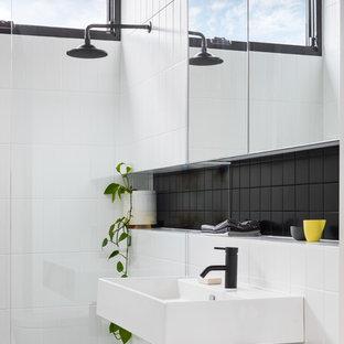 Foto di una stanza da bagno minimal con doccia aperta, piastrelle nere, piastrelle bianche, pareti bianche, lavabo sospeso, pavimento nero e doccia aperta