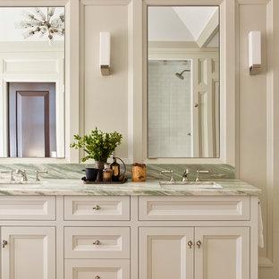 Klassisk inredning av ett stort grön grönt en-suite badrum, med luckor med infälld panel, beige skåp, en toalettstol med hel cisternkåpa, beige väggar, mosaikgolv, ett undermonterad handfat, marmorbänkskiva och grönt golv