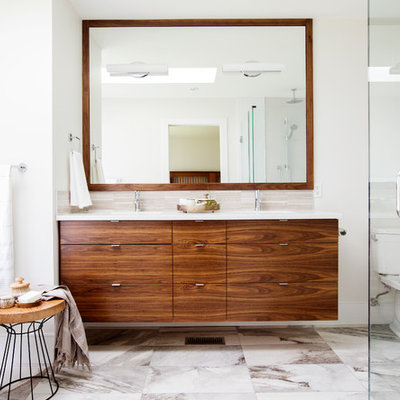 Example of a trendy master beige tile and porcelain tile porcelain tile and multicolored floor bathroom design in Vancouver with flat-panel cabinets, a two-piece toilet, white walls, an undermount sink, quartz countertops, a hinged shower door and medium tone wood cabinets
