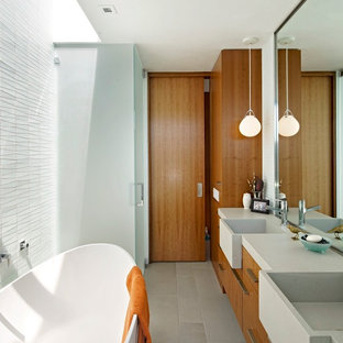 Example of a mid-sized mid-century modern master white tile gray floor and cement tile floor bathroom design in San Francisco with flat-panel cabinets, a hinged shower door, brown cabinets, gray walls, an integrated sink, quartz countertops and beige countertops