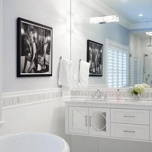 Foto di una grande stanza da bagno padronale chic con consolle stile comò, ante bianche, vasca freestanding, doccia aperta, WC sospeso, piastrelle bianche, piastrelle di vetro, pareti blu, pavimento in marmo, lavabo sottopiano e top in marmo