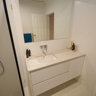 Diseño de cuarto de baño principal, contemporáneo, con armarios tipo mueble, puertas de armario blancas, ducha abierta, baldosas y/o azulejos blancos, baldosas y/o azulejos de porcelana, paredes blancas, suelo de baldosas de porcelana, lavabo bajoencimera, encimera de cuarzo compacto, suelo amarillo, ducha abierta y encimeras blancas