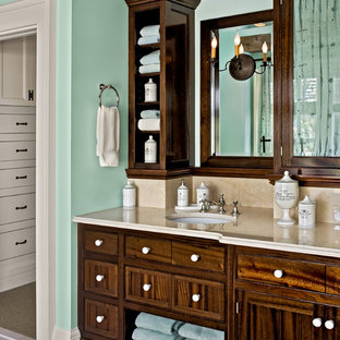 Elegant beige tile bathroom photo in New York with an undermount sink, flat-panel cabinets and dark wood cabinets