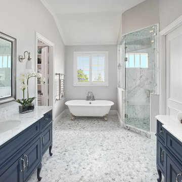 Crisp Master Bathroom with Navy Blue Freestanding Vanities and Claw-foot Tub