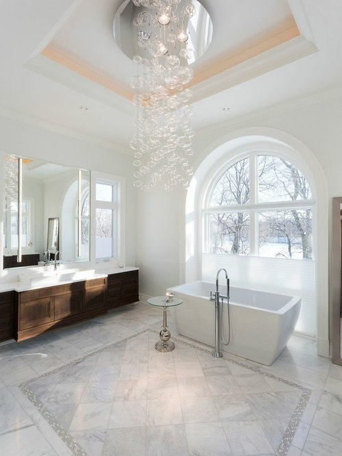 transitional freestanding bathtub idea in vancouver with a vessel sink recessed panel cabinets