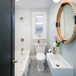 Diseño de cuarto de baño infantil, tradicional, pequeño, con bañera esquinera, combinación de ducha y bañera, sanitario de dos piezas, baldosas y/o azulejos blancos, baldosas y/o azulejos de porcelana, paredes azules, suelo con mosaicos de baldosas, lavabo suspendido y suelo azul