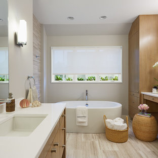 Example of an ornate freestanding bathtub design in Minneapolis with an undermount sink, flat-panel cabinets, medium tone wood cabinets and beige walls