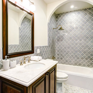Example of a tuscan gray tile mosaic tile floor bathroom design in Los Angeles with an undermount sink, raised-panel cabinets, dark wood cabinets and beige walls