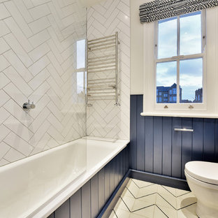 Traditional bathroom in London with blue cabinets, a built-in bath, white tiles, white walls and multi-coloured floors.