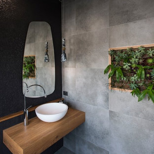 Design ideas for a contemporary 3/4 bathroom in Brisbane with gray tile, black tile, ceramic tile, ceramic floors, a vessel sink, wood benchtops, grey floor, black walls and brown benchtops.