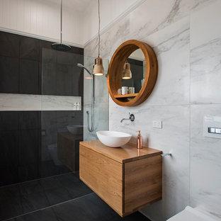 ブリスベンのコンテンポラリースタイルのおしゃれな子供用バスルーム (中間色木目調キャビネット、壁掛け式トイレ、グレーのタイル、黒いタイル、セラミックタイル、白い壁、セラミックタイルの床、ベッセル式洗面器、木製洗面台、オープンシャワー、フラットパネル扉のキャビネット、段差なし、黒い床、ブラウンの洗面カウンター) の写真