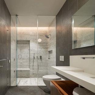 Idéer för att renovera ett funkis badrum, med släta luckor, skåp i mellenmörkt trä, en kantlös dusch, en vägghängd toalettstol, grå väggar, ett väggmonterat handfat, grått golv och dusch med gångjärnsdörr