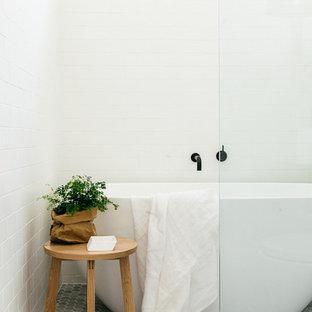 Foto di una piccola stanza da bagno nordica con pareti bianche, vasca freestanding, pavimento con piastrelle a mosaico e piastrelle bianche