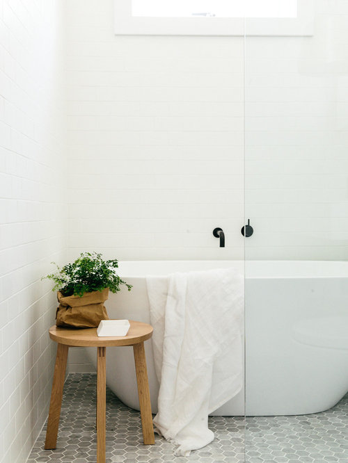 small danish bathroom photo with gray tile white walls a freestanding tub and mosaic