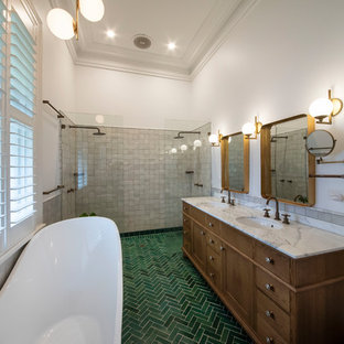Inspiration for a large mediterranean ensuite bathroom in Melbourne with freestanding cabinets, medium wood cabinets, a freestanding bath, a double shower, a one-piece toilet, white tiles, cement tiles, white walls, cement flooring, a submerged sink, marble worktops, green floors, an open shower and white worktops.
