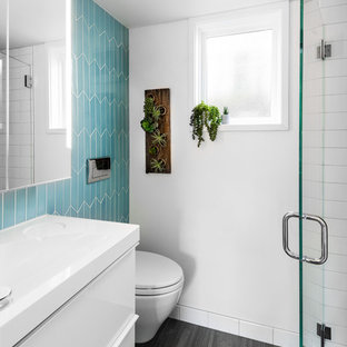 Example of a small trendy 3/4 blue tile and ceramic tile gray floor alcove shower design in Seattle with flat-panel cabinets, white cabinets, a wall-mount toilet, white walls, an integrated sink, solid surface countertops, a hinged shower door and white countertops