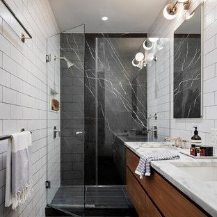 Exemple d'une salle de bain principale tendance avec un placard à porte plane, des portes de placard en bois sombre, un lavabo encastré, un plan de toilette en marbre, une cabine de douche à porte battante, meuble double vasque, meuble-lavabo suspendu et du papier peint.