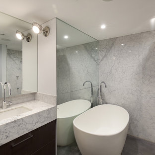 Bathroom - mid-sized transitional master black and white tile and marble tile concrete floor and gray floor bathroom idea in New York with flat-panel cabinets, dark wood cabinets, a wall-mount toilet, blue walls, an undermount sink and marble countertops