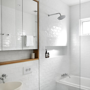 Photo of a contemporary 3/4 bathroom in Sydney with flat-panel cabinets, medium wood cabinets, a drop-in tub, a curbless shower, white tile, subway tile, white walls, a vessel sink, grey floor, an open shower and white benchtops.