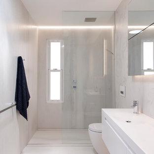 Modelo de cuarto de baño minimalista, de tamaño medio, con lavabo integrado, encimera de acrílico, ducha abierta, sanitario de pared, baldosas y/o azulejos beige, baldosas y/o azulejos de porcelana, paredes beige, suelo de baldosas de porcelana y ducha abierta