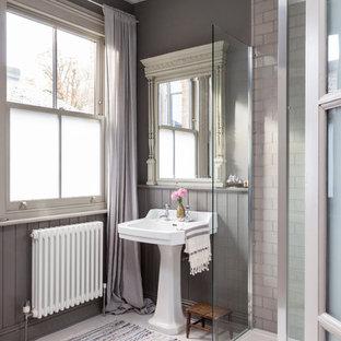 Foto di una stanza da bagno scandinava con lavabo a colonna, doccia ad angolo, piastrelle grigie, piastrelle diamantate e pareti grigie