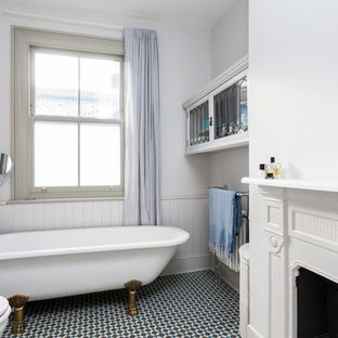 Photo of a scandinavian bathroom in London with a claw-foot bath, white walls, mosaic tile flooring and white cabinets.