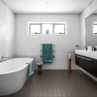 Mid-sized contemporary master bathroom in Sydney with flat-panel cabinets, a freestanding tub, an alcove shower, white walls, solid surface benchtops, brown floor, a hinged shower door, black cabinets, an integrated sink and white benchtops.