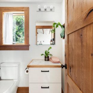 Immagine di una piccola stanza da bagno con doccia design con ante lisce, ante bianche, WC a due pezzi, pareti bianche, pavimento in cemento, top alla veneziana, pavimento grigio e top bianco
