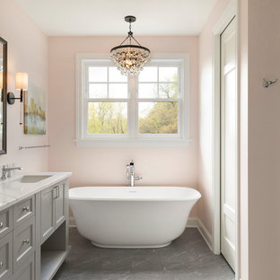 Freestanding bathtub - coastal master white tile and subway tile gray floor freestanding bathtub idea in Minneapolis with shaker cabinets, gray cabinets, pink walls, an undermount sink and white countertops