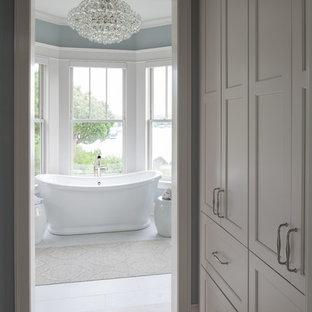 Diseño de cuarto de baño principal, tradicional renovado, grande, con armarios estilo shaker, puertas de armario blancas, bañera exenta, paredes azules, suelo de baldosas de porcelana, lavabo bajoencimera, encimera de granito, suelo blanco y encimeras grises