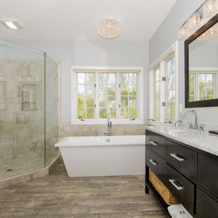 Example of a mid-sized transitional master beige tile and ceramic tile porcelain floor and brown floor bathroom design in DC Metro with an undermount sink, shaker cabinets, dark wood cabinets, granite countertops, a two-piece toilet, blue walls and a hinged shower door